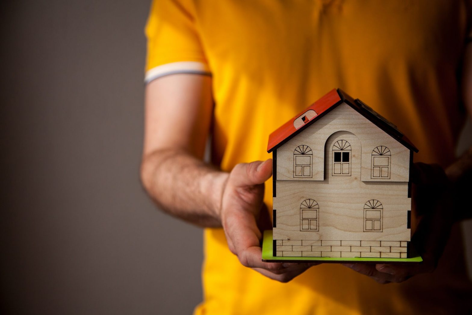 man holding a toy wooden house in his hands