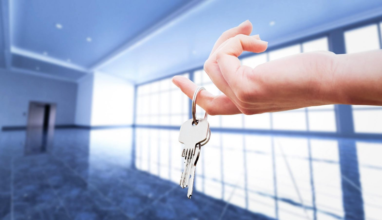womans hand holding the keys to an apartment